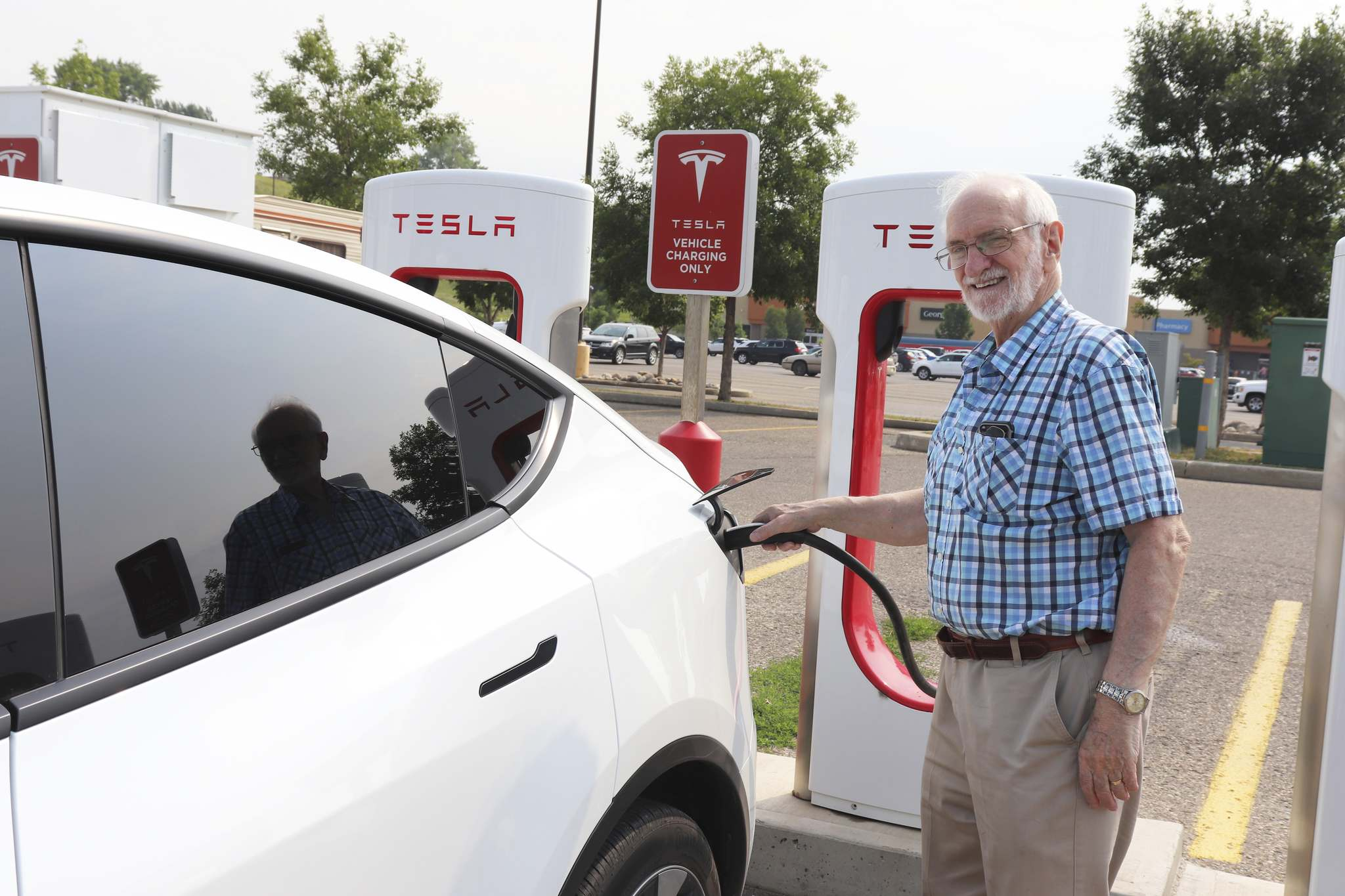 Norman powers up his 2020 Tesla Model Y at Brandon's Tesla Supercharger station at the Corral Centre on Wednesday. (Kyle Darbyson/The Brandon Sun)