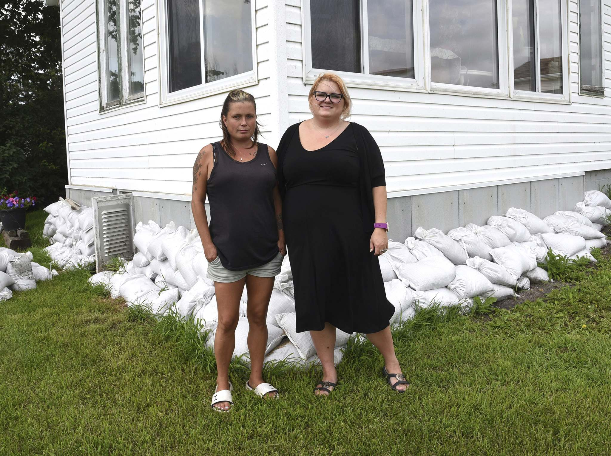 Cherisse Olenick and her sister Stephanie Shaw stand beside the house where the explosion that burned Olenick's husband Mark occurred. (Bud Robertson/The Brandon Sun)