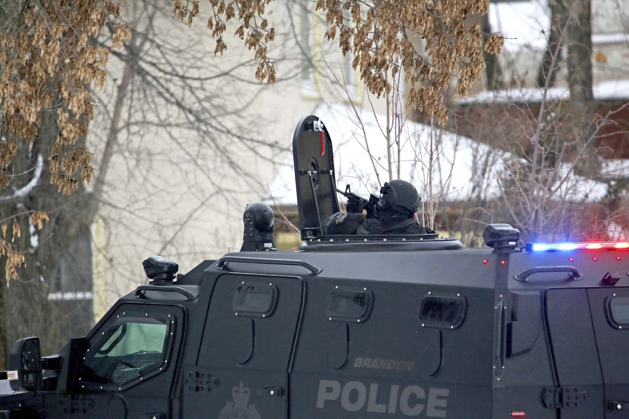 An armed Brandon Police officer covers a multi-suited residence on 15th Street from the rooftop port of the force's armoured rescue vehicle earlier this year. (File)