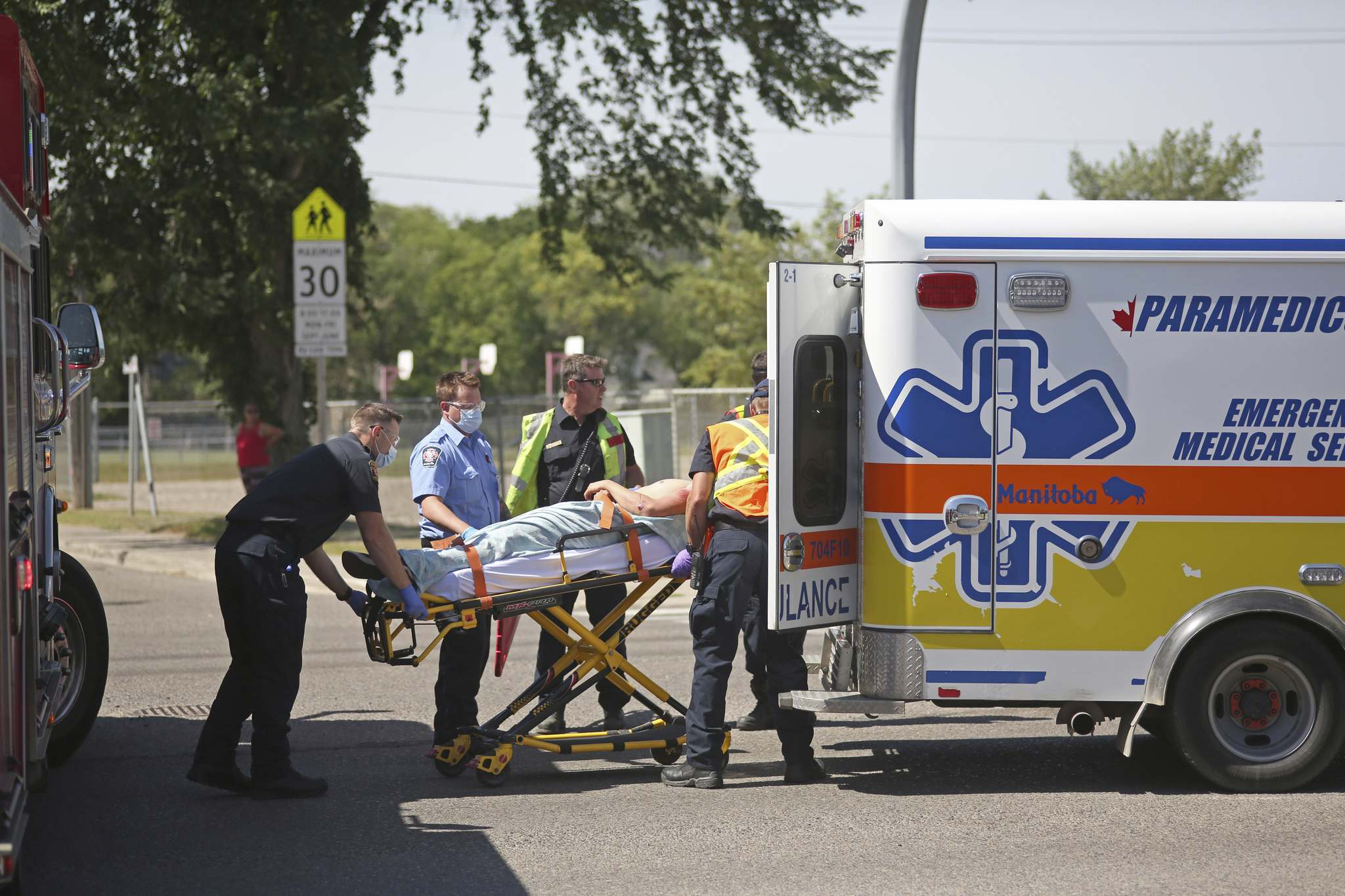 Emergency crews load an injured man into the back of an ambulance at the corner of 18th Street and McTavish Avenue on Wednesday afternoon. (Matt Goerzen/The Brandon Sun)