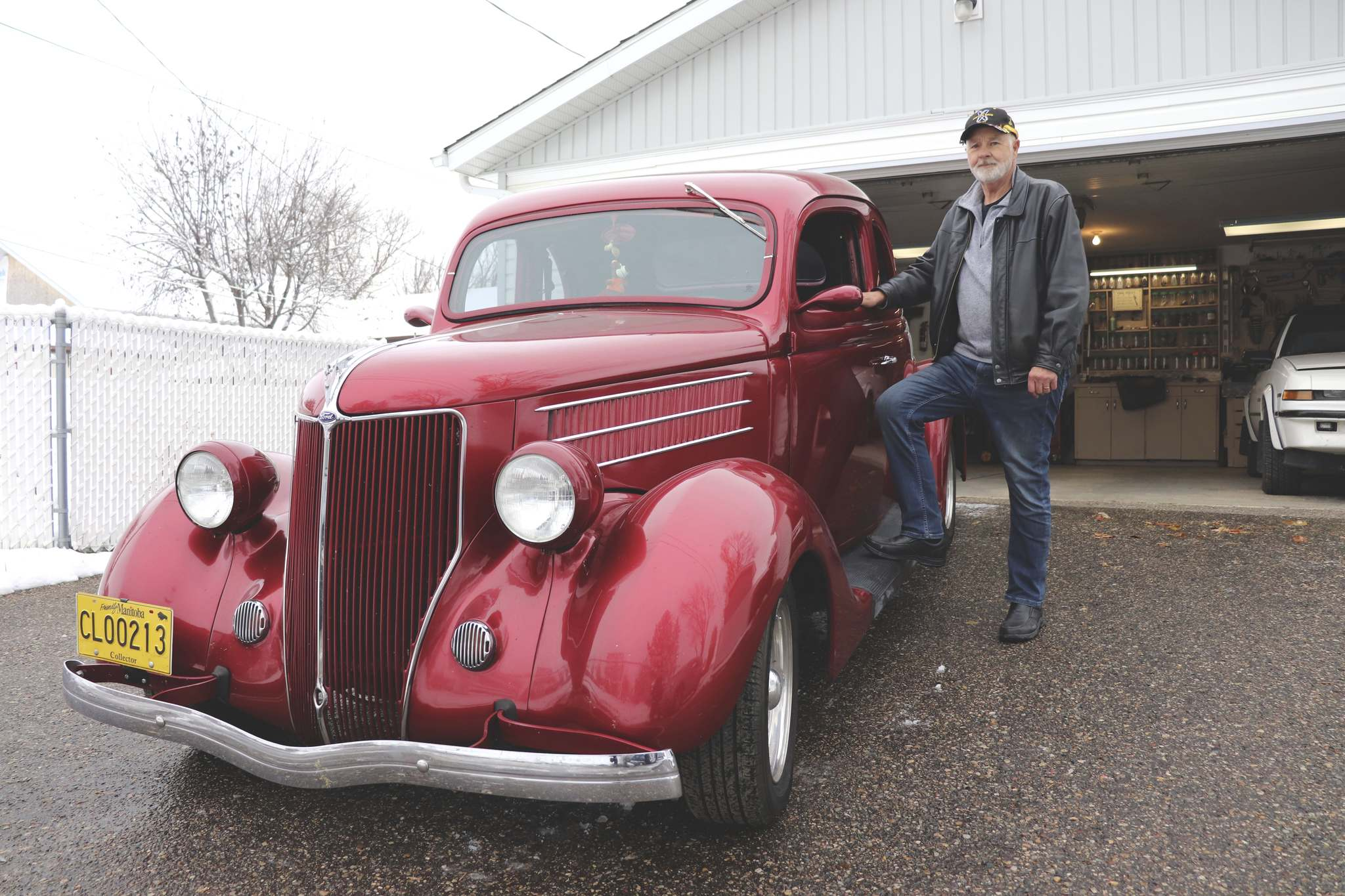 TOP: Brandon resident Roger Plowman poses for a photo next to his 1936 Ford Coupe on Wednesday afternoon. BOTTOM: Roger Plowman gets behind the wheel of his 1936 Ford Coupe alongside Rooty, the A&W Great Root Bear, on Wednesday afternoon. (Photos by Kyle Darbyson/The Brandon Sun)</p></p>