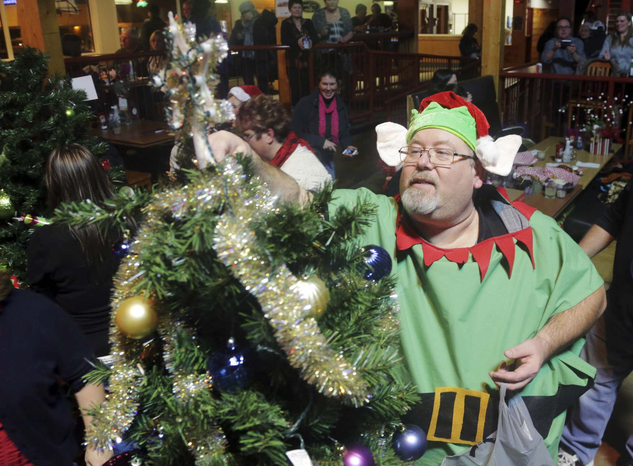 Glen Johnston, clad as an elf, helps decorate a Christmas tree during the Brandon and District United Way's 19th annual Tree Auction in 2014. Despite the additional health restrictions announced on Thursday for Manitoba, the Brandon & District United Way has found a way for its annual Christmas tree auction to go ahead this year. (File)</p></p>