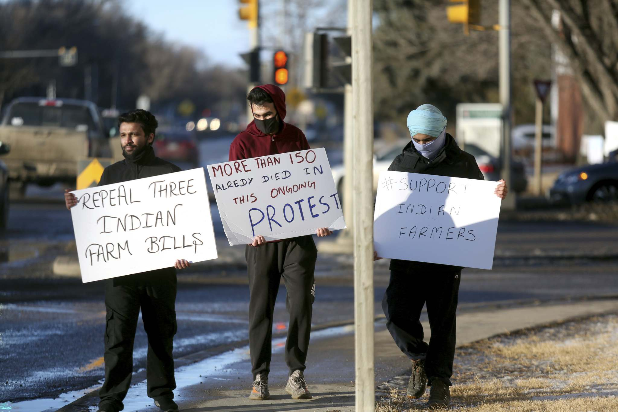 Kanwar Suagh, Taranveer Singh and Gagandeep Singh, from left, hold their signs in protest of India's government at the corner of 18th Street and Victoria Avenue on Monday. (Tyler Clarke/The Brandon Sun)</p></p>