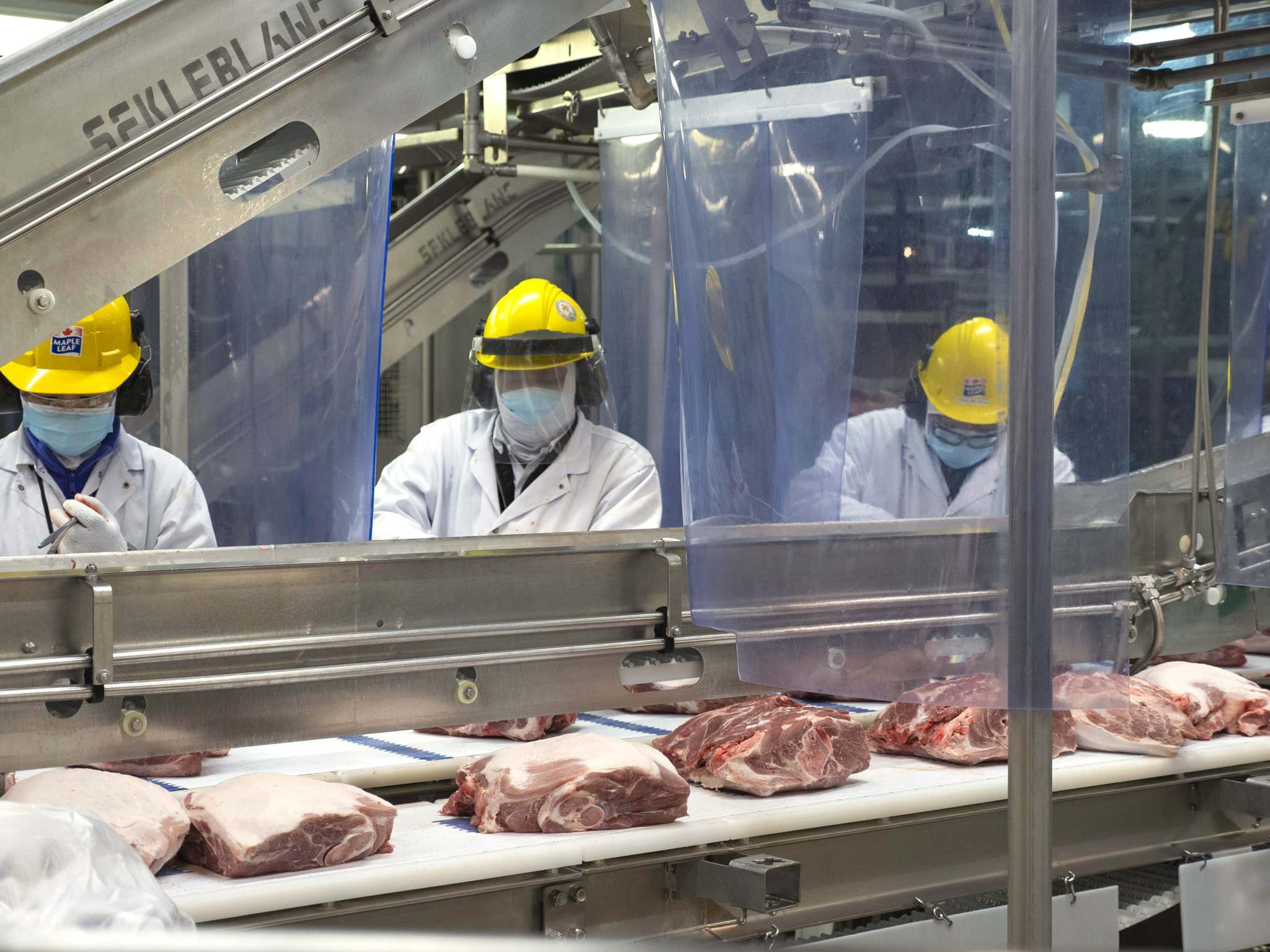 Maple Leaf Foods employees are seen wearing protective gear while working at Brandon's pork processing plant. (Submitted)