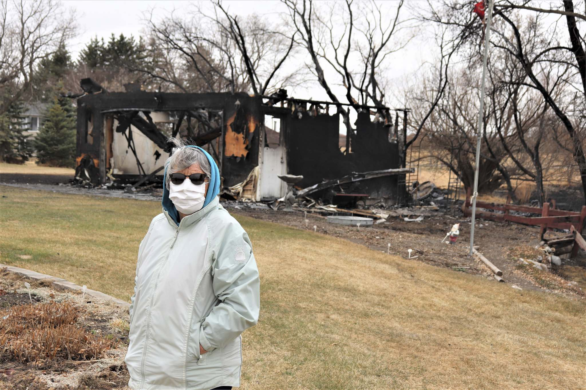 Rapid City resident Edie Evans is seen in front of her burnt-out garage on Sunday afternoon, nearly 24 hours after it caught fire due to a controlled burn gone awry. (Kyle Darbyson/The Brandon Sun)
