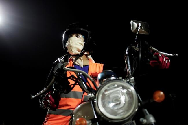 In this June 23, 2018 photo, Maha Mohammed poses for a photograph on a motorbike as she learns how to ride, at the Bikers Skills institute in Riyadh, Saudi Arabia. As Saudi Arabia prepares to lift a ban on women driving, Saudi women are being pushed to the forefront of a major transformation being spearheaded by the country's Crown Prince Mohammed bin Salman. It also places women in the crosshairs of a decades-old pull-and-tug between Saudis agitating for more social openings and a majority that remains deeply conservative. (AP Photo/Nariman El-Mofty)
