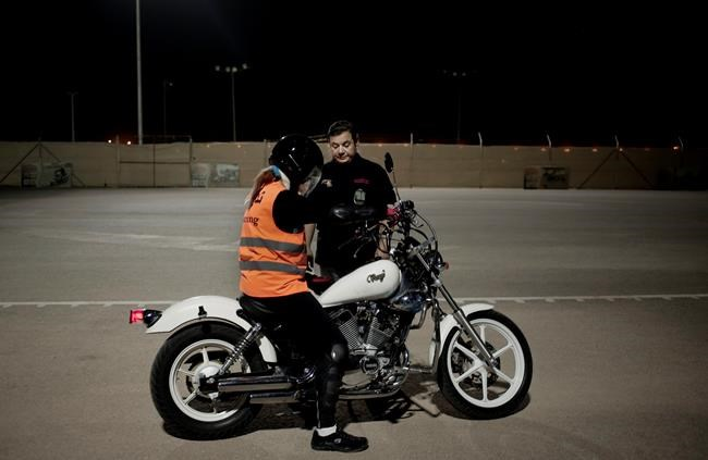 In this June 23, 2018 photo, instructor and general manager, Wael Bin Huraib, right, teaches Maha Mohammed how to ride a motorbike, at the Bikers Skills institute in Riyadh, Saudi Arabia. While there was never explicitly a law against women driving in Saudi Arabia, a ban was enforced by police and licenses were not issued to women. The ban had been a stain on the country's reputation and hindered women's ability to contribute to the economy. (AP Photo/Nariman El-Mofty)