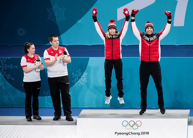 Canadians Kaitlyn Lawes, centre, and John Morris, right, react after winning gold as Switzerland teammates Jenny Perret, left, and Martin Rios, second left, look on during mixed doubles curling medal ceremony at the 2018 Olympic Winter Games in Gangneung, South Korea on Tuesday, February 13, 2018. THE CANADIAN PRESS/Nathan Denette