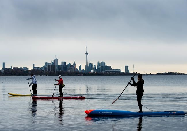People physical distance while stand-up paddleboarding in Humber Bay on Lake Ontario during the COVID-19 pandemic in Toronto on Sunday, May 10, 2020. THE CANADIAN PRESS/Nathan Denette