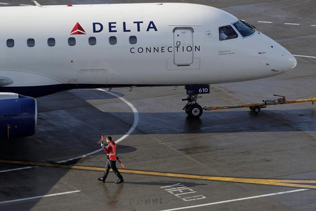 FIE - In this Feb. 5, 2019, file photo a ramp worker guides a Delta Air Lines plane at Seattle-Tacoma International Airport in Seattle. Delta Air Lines says it earned $1.1 billion in the fourth quarter by operating more flights and filling a higher percentage of seats. The financial results beat Wall Street expectations. Delta and other U.S. airlines are enjoying a prolonged period of profitability thanks to steadily rising demand for travel. (AP Photo/Ted S. Warren, File)