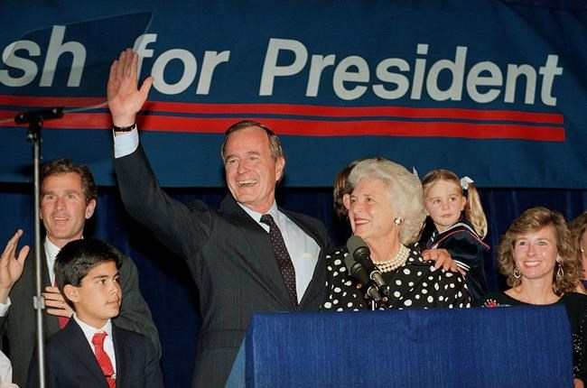 FILE - In this Oct. 12, 1987, file photo, then-Vice President George H.W. Bush and his wife Barbara, with their son George W. Bush, far left, wave to supporters who turned out in Houston, to hear him announce he was a candidate for the Republican nomination for president of the United States.