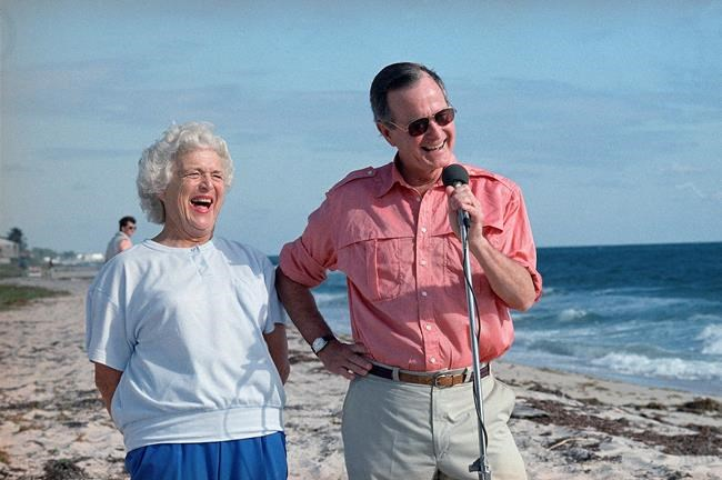 In this Nov. 14, 1988, file photo, President-elect George H.W. Bush and his wife, Barbara, are shown during a morning beachfront news conference in Gulf Stream, Fla.