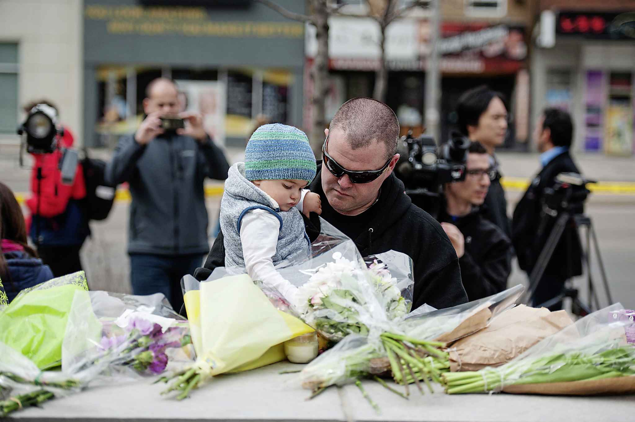 Sean O'Keefe and his son Fionn, 16 months, bring flowers to a memorial on Yonge Street the day after a driver drove a rented van down sidewalks Monday afternoon, striking pedestrians in his path in Toronto, Tuesday, April 24, 2018. THE CANADIAN PRESS/Galit Rodan