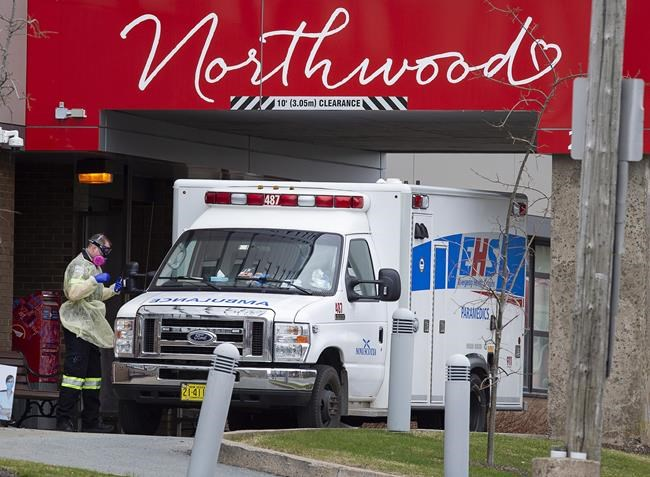 A paramedic walks around an ambulance at Northwood Manor, one of the largest nursing homes in Atlantic Canada with 585 residents, in Halifax on Friday, May 1, 2020. The death toll in Nova Scotia associated with the COVID-19 pandemic continues to grow. Health officials confirmed Thursday that another resident of the Northwood long-term-care facility in Halifax has died, bringing the province's overall total to 58. THE CANADIAN PRESS/Andrew Vaughan