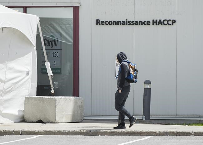 A man walks into a Cargill meat processing plant in Chambly, Que., south of Montreal, Sunday, May 10, 2020. A group representing Canada's meat-packing industry is expecting more changes in the coming months to make sure workers have protection from the COVID-19 pandemic. THE CANADIAN PRESS/Graham Hughes