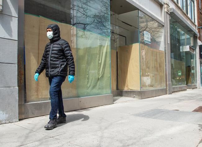 A pedestrian walks past closed storefronts on Ste. Catherine street Wednesday April 22, 2020 in Montreal.THE CANADIAN PRESS/Ryan Remiorz