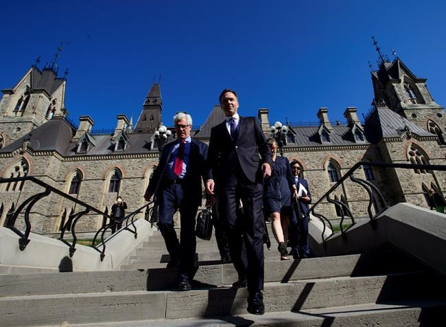 Natural Resources Minister James Carr and Finance Minister Bill Morneau leave a cabinet meeting on route to the National Press Theatre in Ottawa on Tuesday, May 29, 2018. Finance Minister Bill Morneau says Canada is going to buy the Trans Mountain pipeline and all of Kinder Morgan Canada's core assets for $4.5 billion. THE CANADIAN PRESS/Sean Kilpatrick