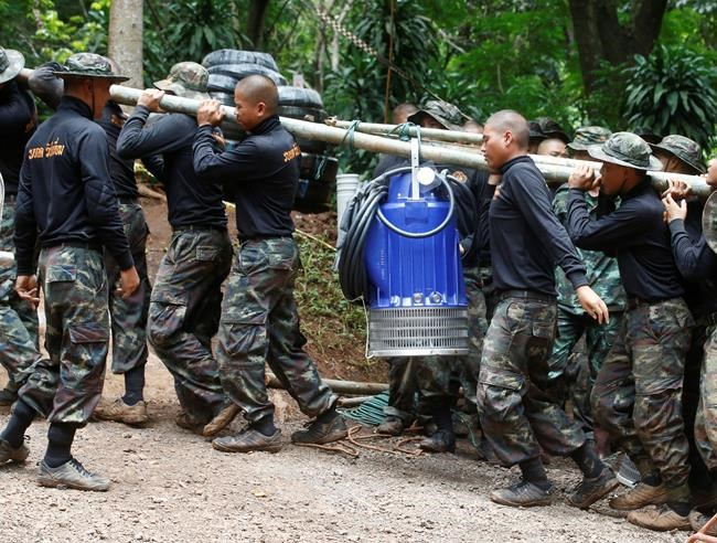 Soldiers carry a pump to help drain the rising flood water in a cave where 12 boys and their soccer coach have been trapped since June 23, in Mae Sai, Chiang Rai province, in northern Thailand Friday, July 6, 2018. Thai authorities are racing to pump out water from the flooded cave before more rains are forecast to hit the northern region. (AP Photo/Sakchai Lalit)