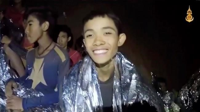 In this July 3, 2018, image taken from video provided by the Royal Thai Navy Facebook Page, a Thai boy smiles as Thai Navy SEAL medic help injured children inside a cave in Mae Sai, northern Thailand. The Thai soccer teammates stranded more than a week in the partly flooded cave said they were healthy on a video released Wednesday, as heavy rains forecast for later this week could complicate plans to safely extract them. (Royal Thai Navy Facebook Page via AP)