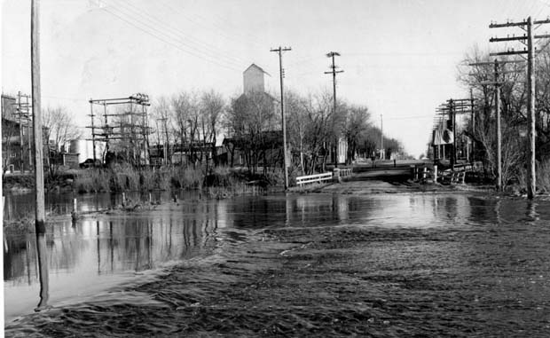 Flood waters from Bosshill and Gopher Creeks, tributaries of the Assiniboine River, this week flowed across the No. 22 highway at its entrance to Virden. (Winnipeg Tribune Archives, 1954?)