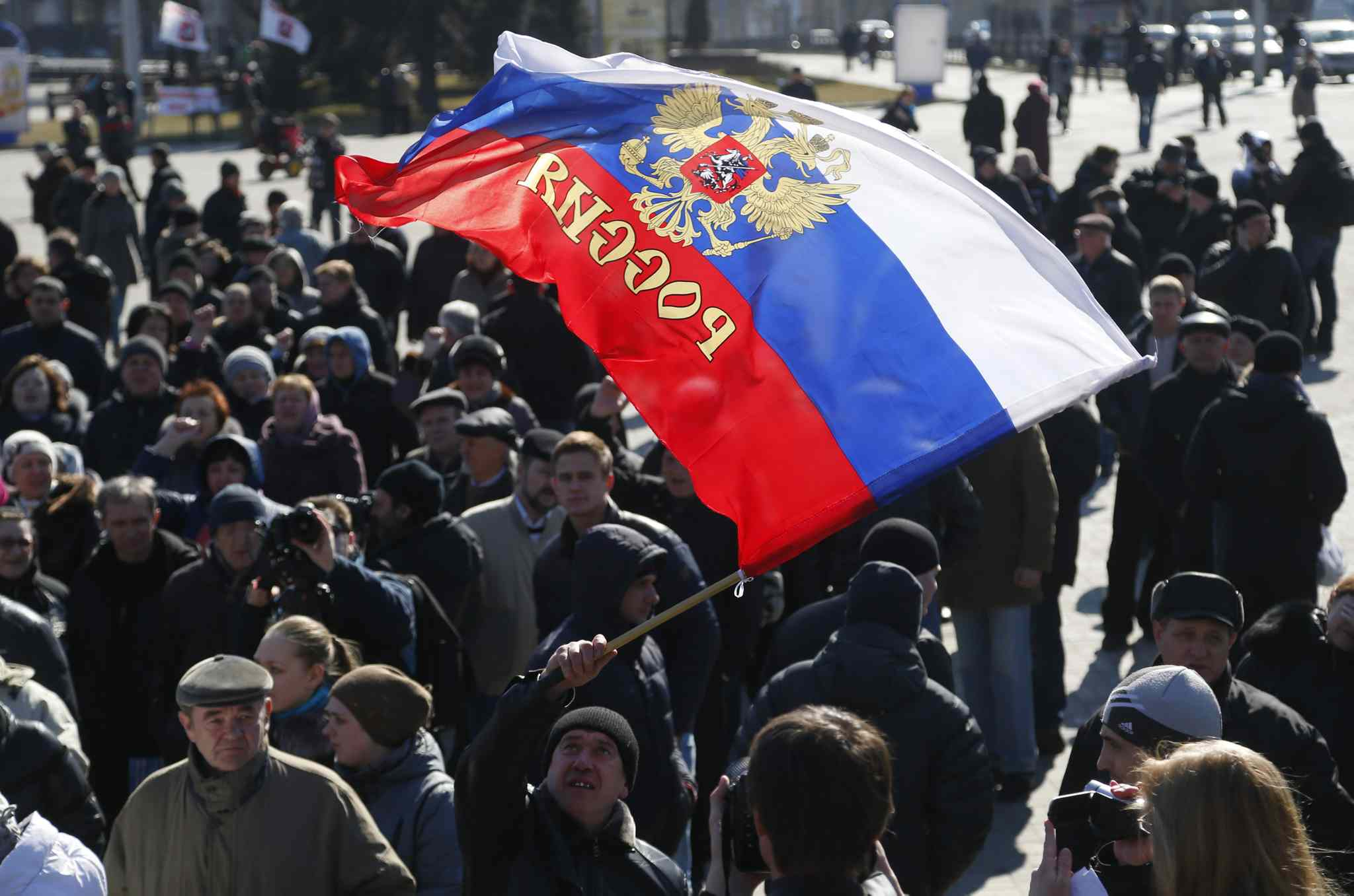 A man waves a Russian flag during a pro Russian rally at a central square in Donetsk, eastern Ukraine, Monday. Many Russian-speakers in the region continue to protest against the new Ukrainian government following the overthrow of pro-Kremlin President Viktor Yanukovych.