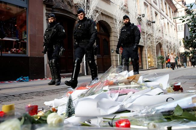 French police officers patrol in the streets front of flowers to pay respects of the victims following an attack killing three persons and wounding at least 13, in Strasbourg, eastern France, Thursday, Dec. 13, 2018. Police union officials identified the suspected assailant as Frenchman Cherif Chekatt, a 29-year-old with a thick police record for crimes including armed robbery and monitored as a suspected religious radical by the French intelligence services. (AP Photo/Christophe Ena)