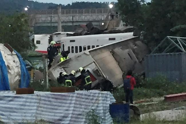 In this photo released by Li Jun, rescue workers are seen at the site of a train derailment in Lian in northern Taiwan on Sunday, Oct. 21, 2018. The Puyuma express train was carrying more than 300 passengers toward Taitung, a city on Taiwan's southeast coast, when it went off the tracks on Sunday afternoon. (Li Jun via AP)