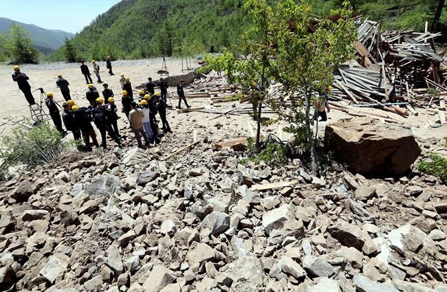 In this Thursday, May 24, 2018 photo, North Korean officials and members of foreign media stand near rubble after explosion at North Korea's nuclear test site in Punggye-ri, North Korea. North Korean leader Kim Jong Un made good on his promise to demolish his country's nuclear test site, which was formally closed in a series of huge explosions Thursday as a group of foreign journalists looked on. (Korea Pool/Yonhap via AP)