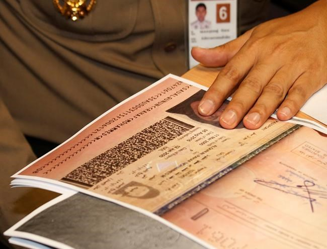 A passport copy of Rahaf Mohammed Alqunun sits on the desk as Chief of Immigration Police Maj. Gen. Surachate Hakparn talks to media about her status during a press conference at the Suvarnabhumi Airport in Bangkok Monday, Jan. 7, 2019. Thailand's Immigration Police chief says Alqunun, the young Saudi woman stopped in Bangkok as she was trying to escape alleged abuse by her family by traveling to Australia for asylum, will not be sent anywhere against her wishes. (AP Photo/Sakchai Lalit)
