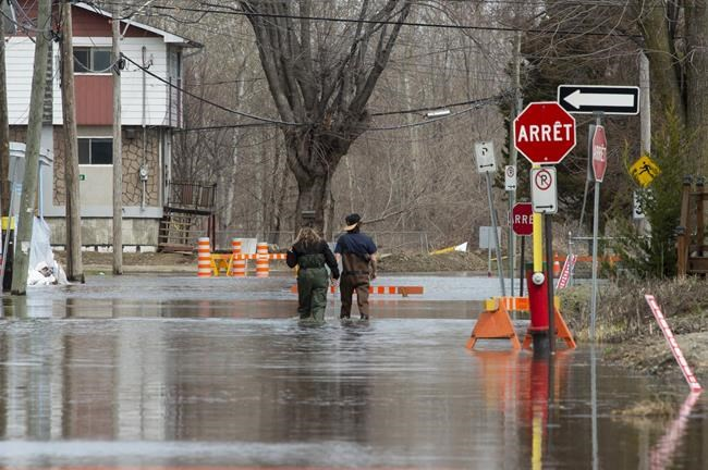 Local residents make their way through flood waters in Gatineau, Que., Tuesday, April 23, 2019. Infrastructure Minister Francois-Philippe Champagne says he is willing to fast-track reviews of projects that could help communities mitigate the impacts of rising flood waters as part of an offer to provinces and cities today. THE CANADIAN PRESS/Adrian Wyld