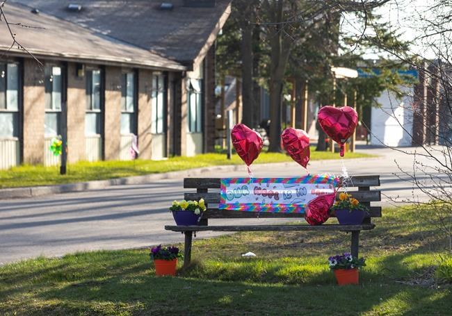 A bench adorned with balloons and flowers stands outside Orchard Villa Care home, in Pickering, Ont. on Saturday, April 25, 2020. THE CANADIAN PRESS/Chris Young
