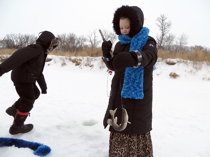 """Following a morning of learning about fish species, habitat, regulations and ice safety, young anglers take to the ice to do a little catch-and-release fishing during the Assiniboine Hills Conservation District's """"Ice Fishing Days."""""""