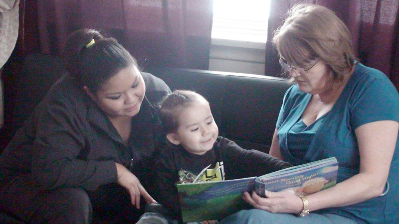 A Home Visitor reads and plays with a child and mother as part of the Parent-Child Home Program, a unique early literacy program.
