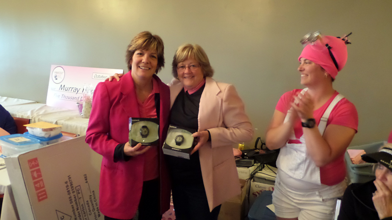 Carol Dalrymple and Colleen Nelson show off their prizes for winning the championship flight under the watchful eye of tournament booster Stacie Popien.